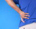 young man in blue shirt suffering back pain